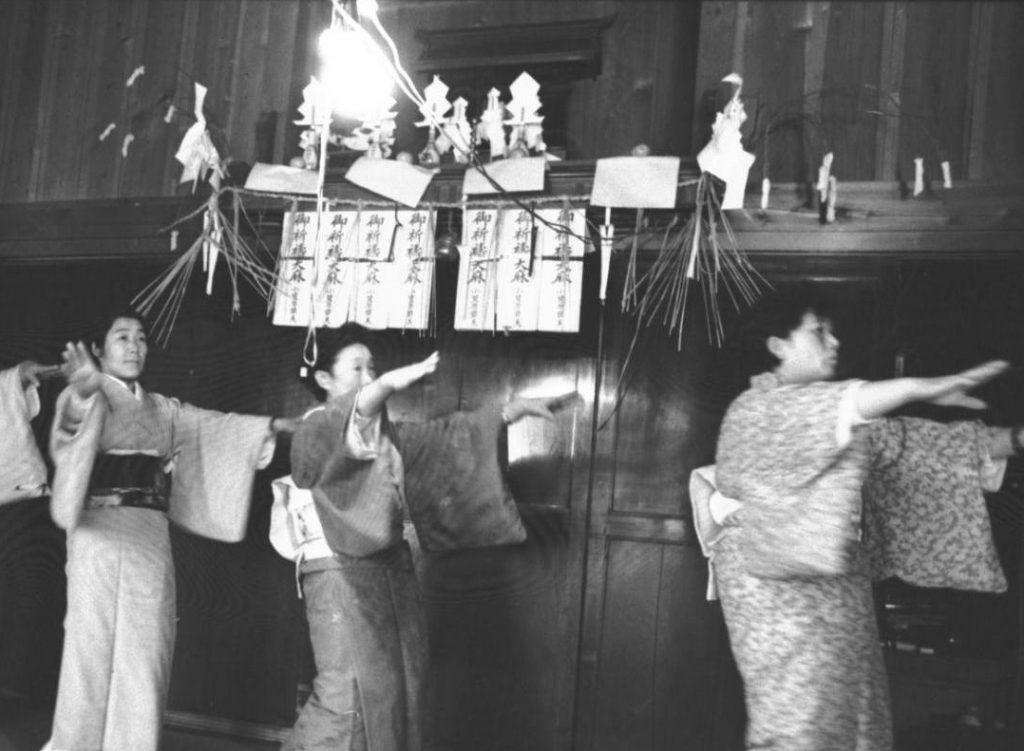 写真下:神棚の前で手踊りをする女性たち